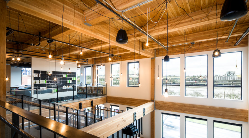 38 Davis, a mixed-use building in Portland, Oregon, features a timber frame structure with exposed glulam beams over a concrete podium. Additional exposed wood, brick and concrete elements throughout provide a distinct warehouse appeal in the open-layout office spaces, apartment units and community areas. Image Courtesy of Ankrom Moisan Architects