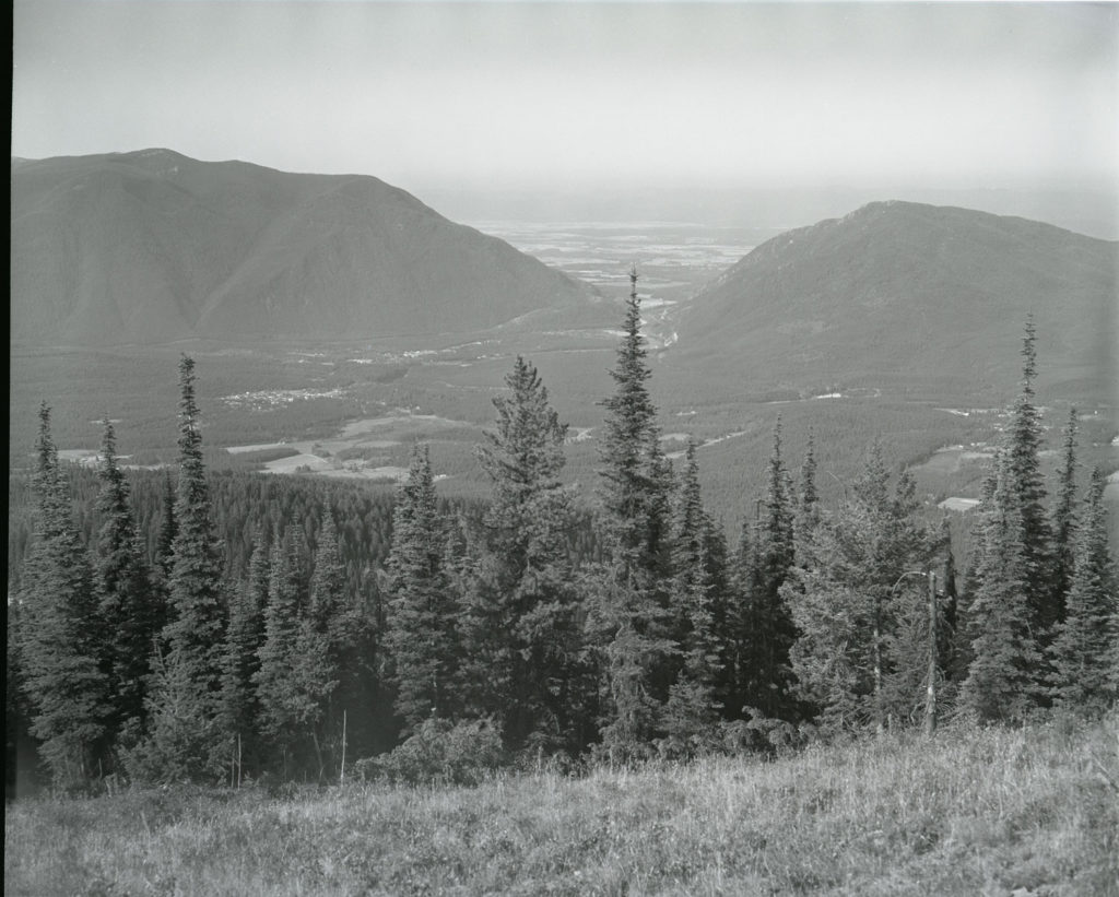 A photo of the same valley more than 40 years later mostly covered in lodgepole pine and Douglas fir. The photo is hazy because of smoke from a nearby wildfire. Date: 08/28/1981 Credit: George Gruell (USFS) Archived at the Mansfield Library at the University of Montana